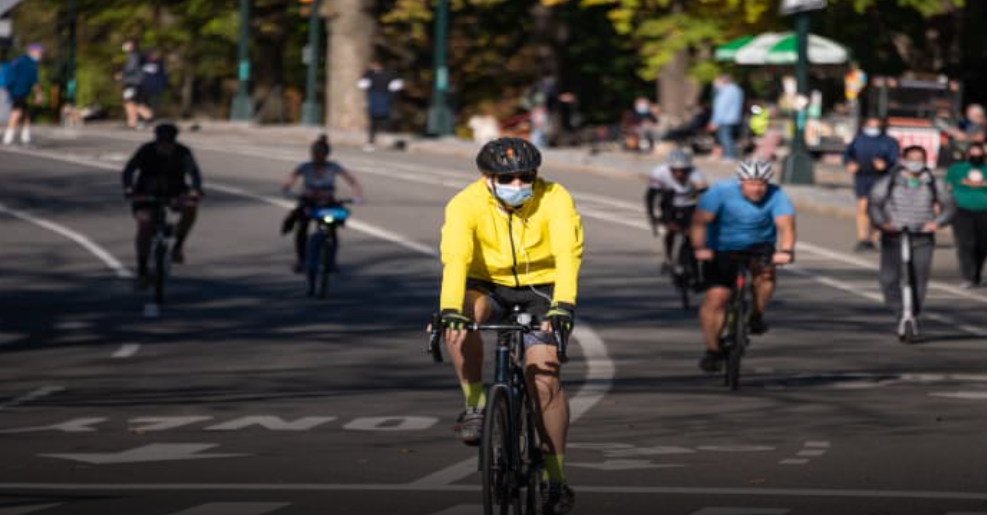 Man in yellow jacket biking with other bicyclists in the background